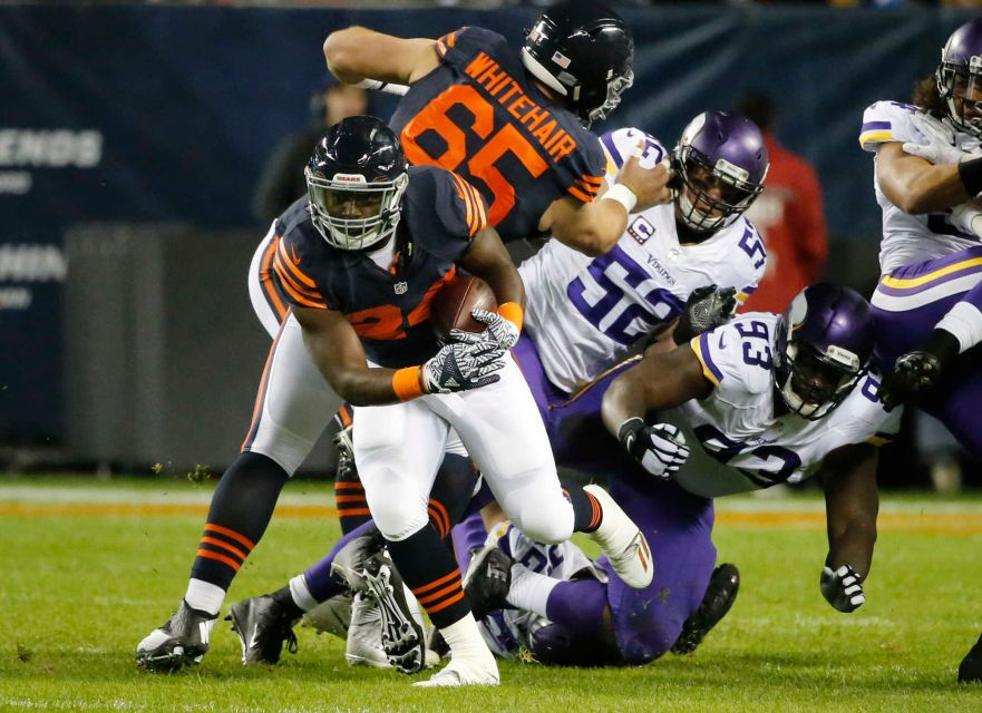 Jordan Howard runs through an open lane created by the Bears offensive line. (Image Credit: AP / Charles Rex Arbogas)